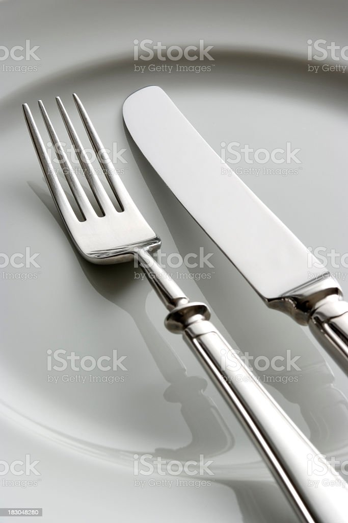Close-up of fork and knife on white plate. royalty-free stock photo