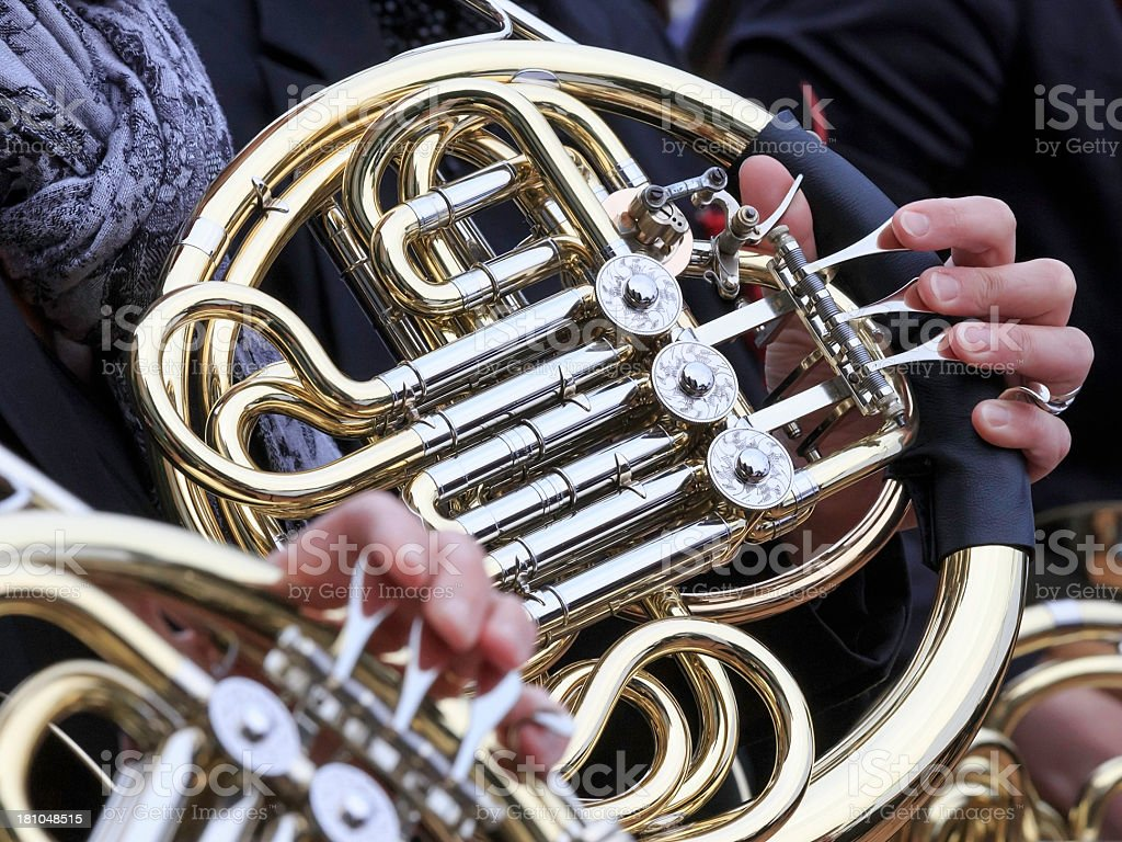 Close-up of French horn playing in orchestra at outdoor concert royalty-free stock photo