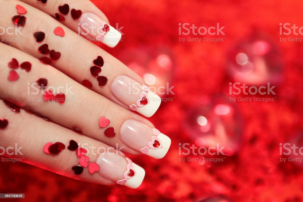 Close-up of French manicured nails and tiny ready hearts stock photo