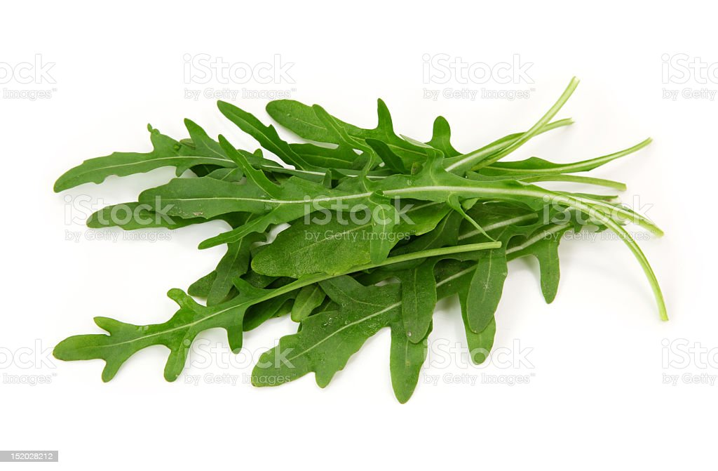 Close-up of fresh arugula leaves over a white background stock photo