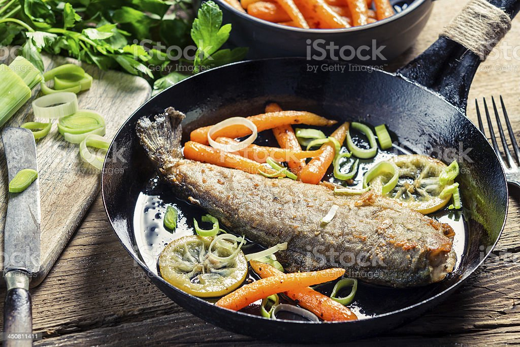 Closeup of freshly fried fish with leek and carrot stock photo