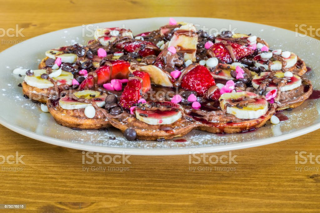 Closeup of fruity Belgian waffles with  chocolate and strawberry sauce stock photo