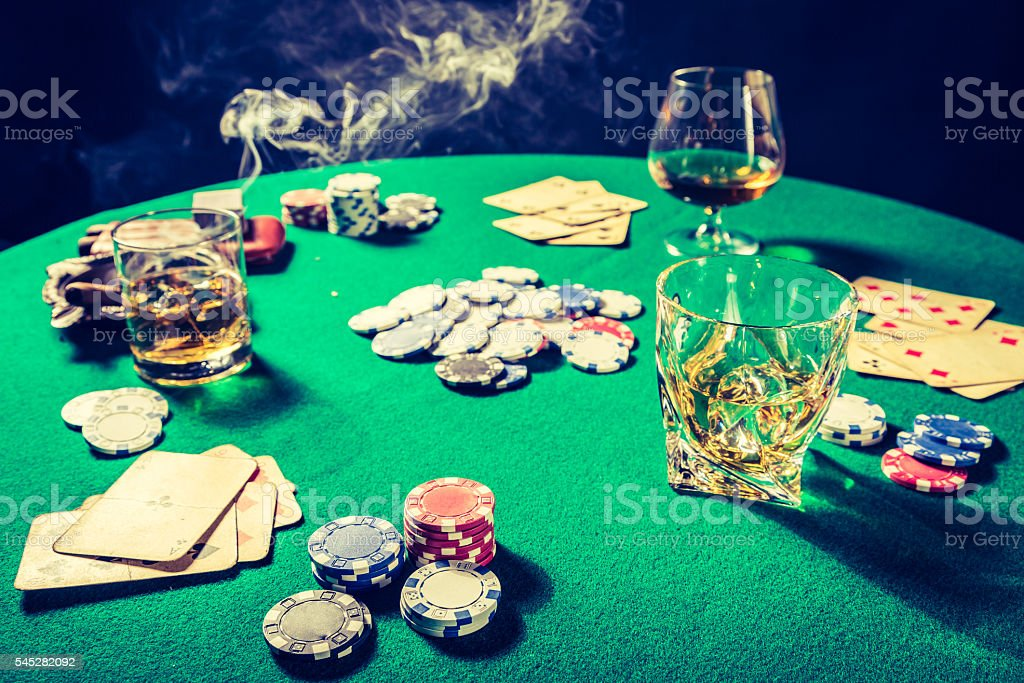 Closeup of gambling table with whiskey, cigar and cards stock photo