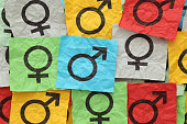 Close-up of gender symbols on colorful paper
