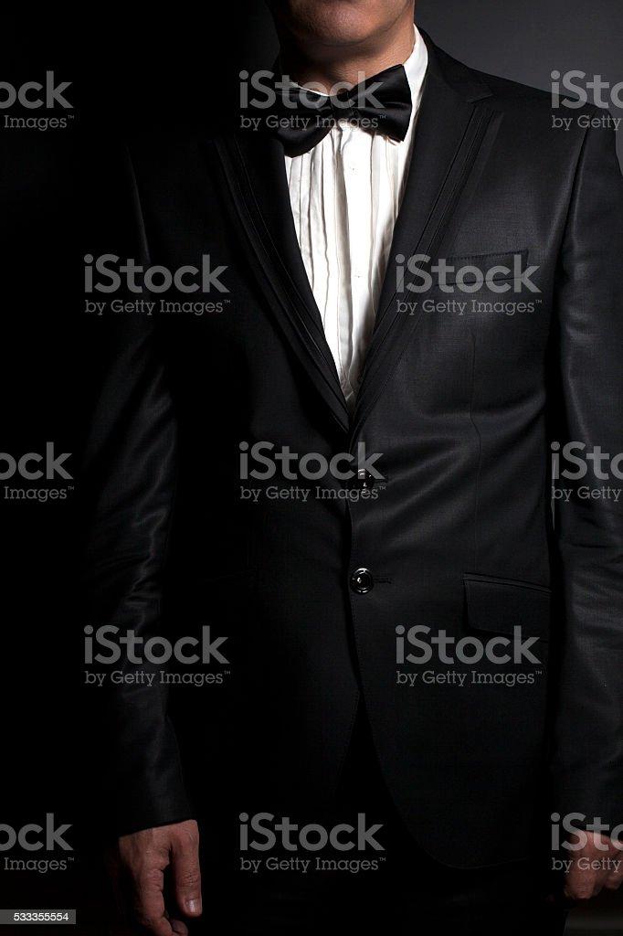 Close-up of gentleman wearing black tie straightens his bowtie stock photo