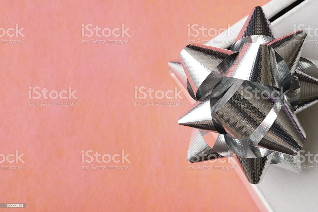 Close-up of gift box with silver ribbon on pink background royalty-free stock photo