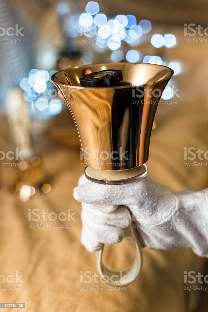 Close-up of girl holding metal bell in hand stock photo