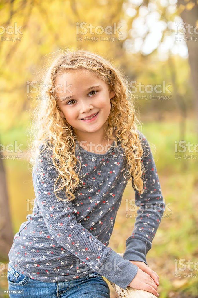 Close-Up of Girl With Curly Blonde Hair in Autumn stock photo