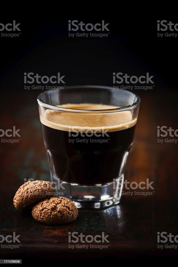Close-up of glass of espresso with small cookies stock photo