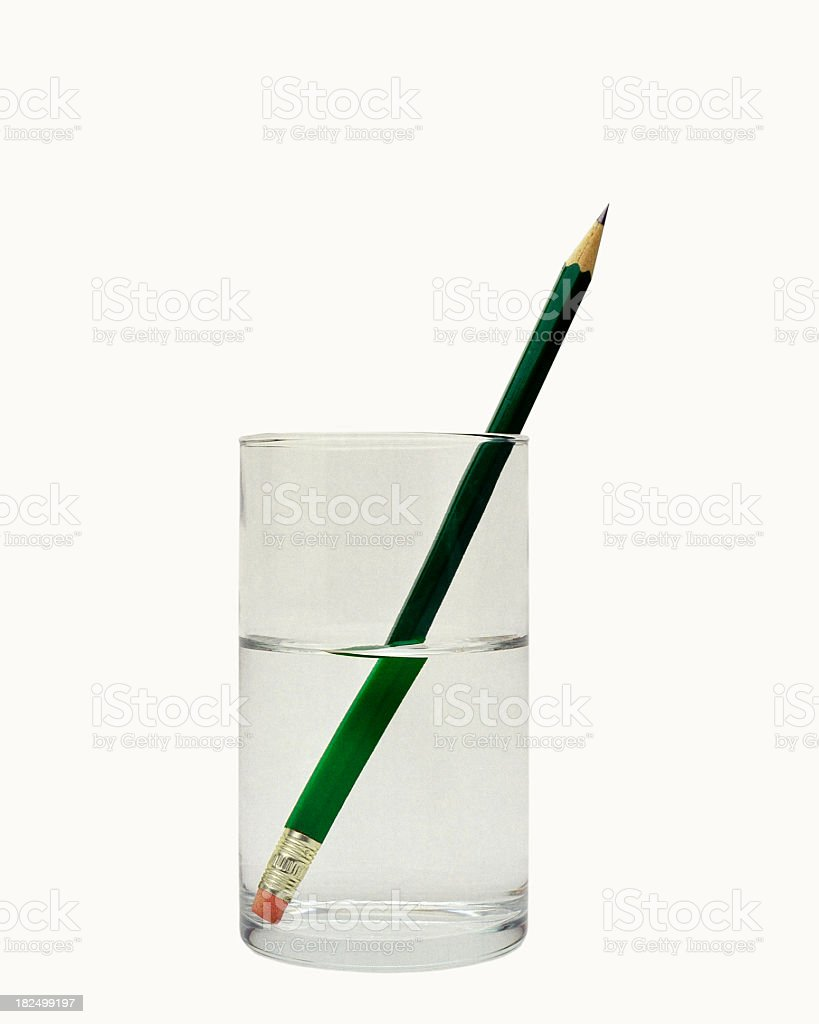 Close-up of glass of water with a green pencil inside it stock photo