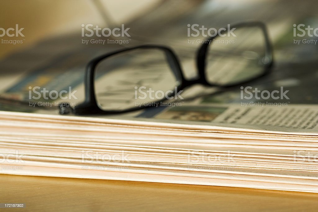 Close-up of glasses on top of stack of newspapers stock photo