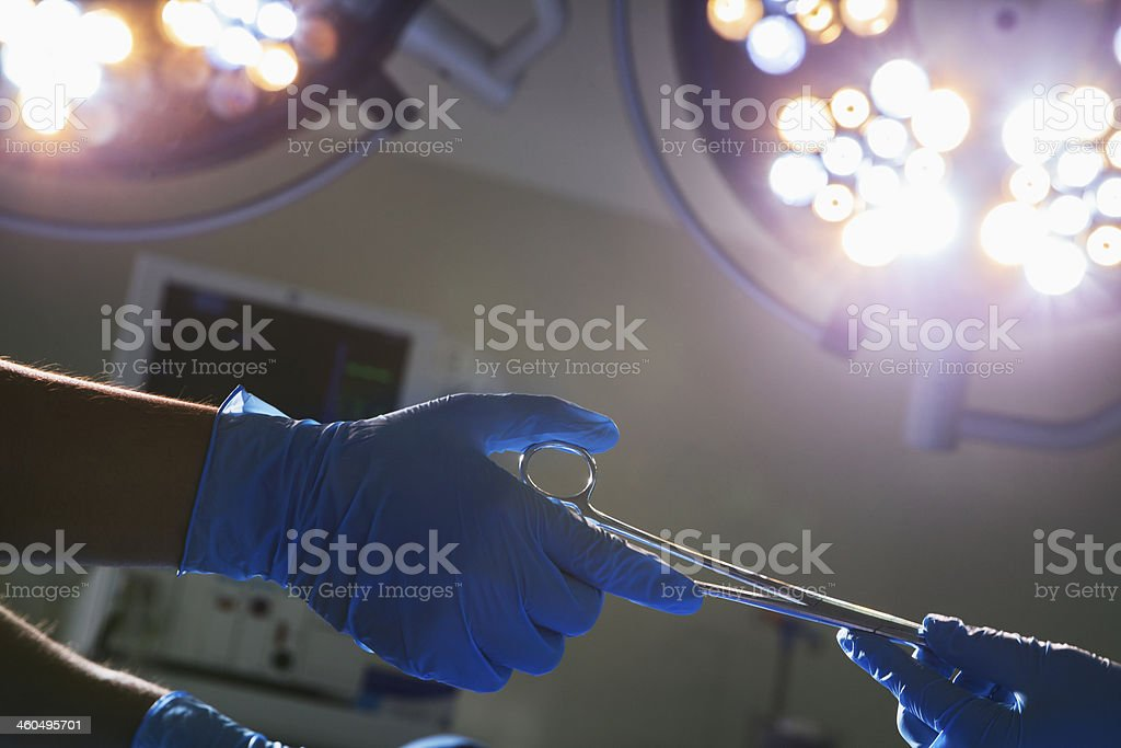 Close-up of gloved hands passing the surgical scissors stock photo