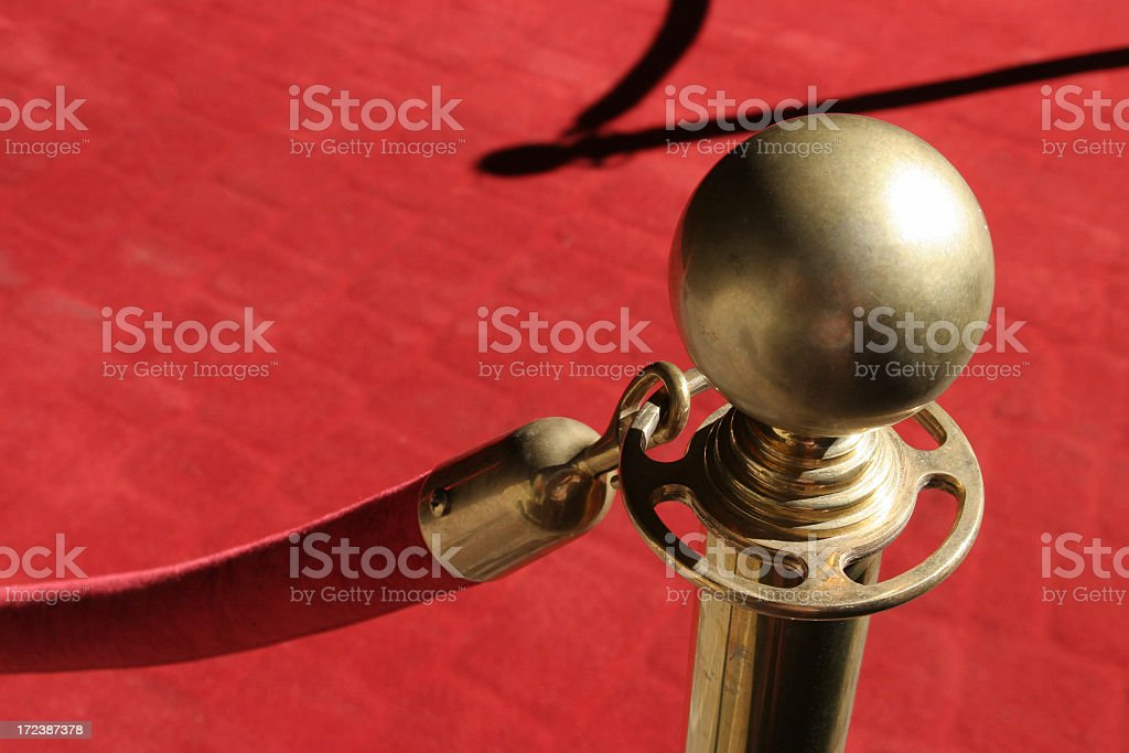 Close-up of gold stanchion holding red rope over red carpet stock photo