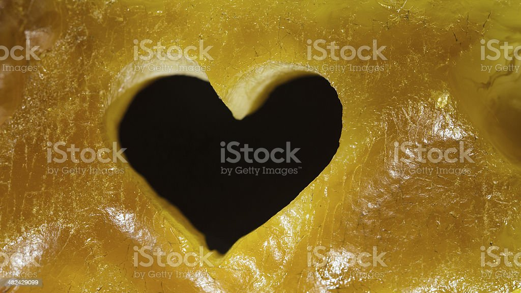Closeup of golden amber with heart love symbol as background stock photo