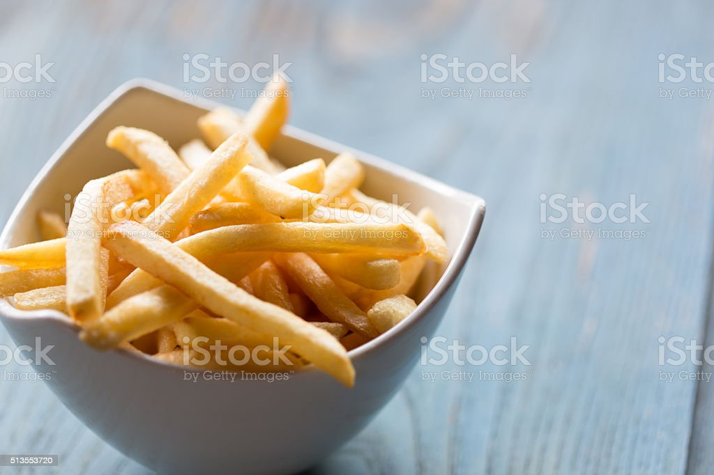 Close-Up of Golden French Fries in a White Bowl stock photo