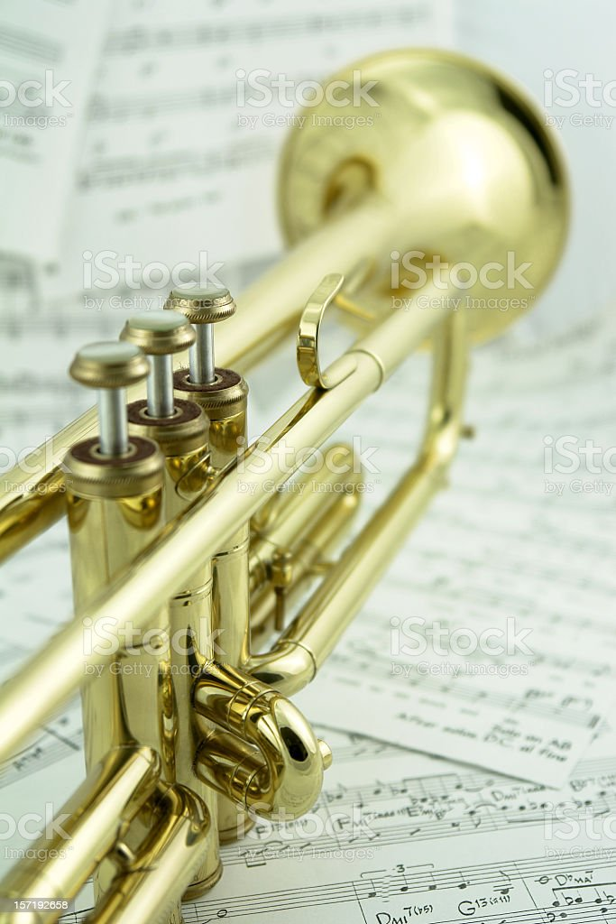 Close-up of golden trumpet standing on music notes, rear view royalty-free stock photo