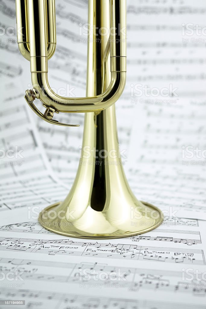 Close-up of golden trumpet standing on music notes, side view royalty-free stock photo