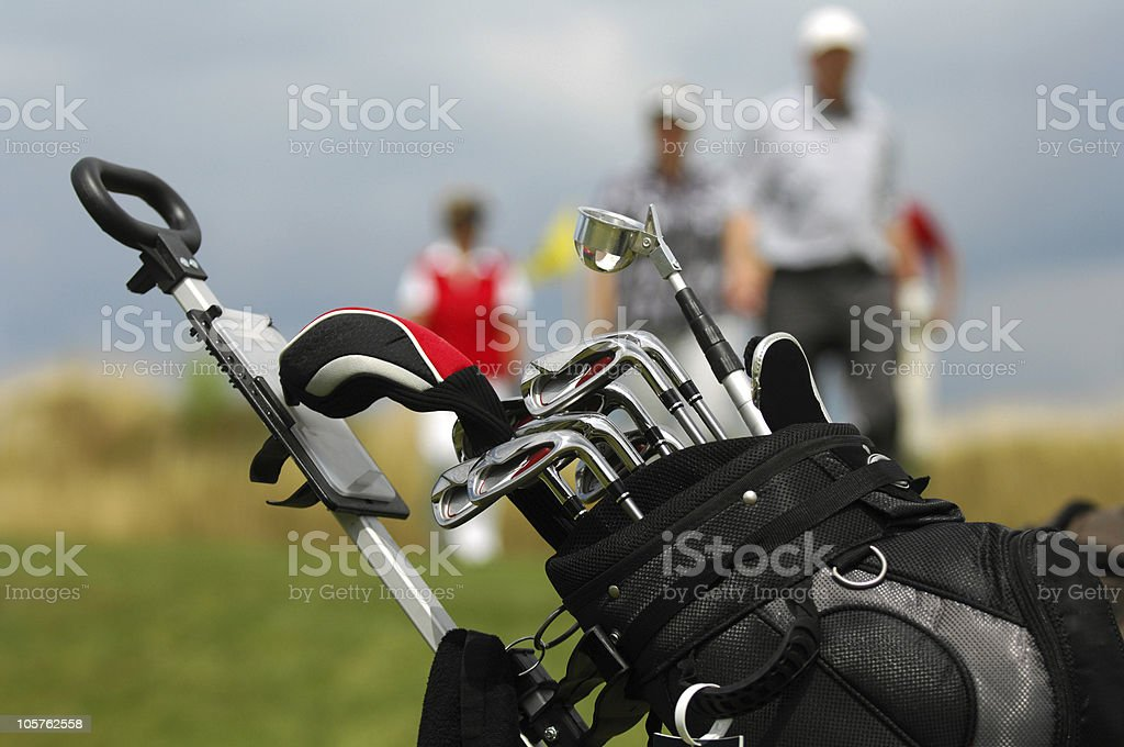 Close-up of golf bag with clubs with golfers blurred in back stock photo