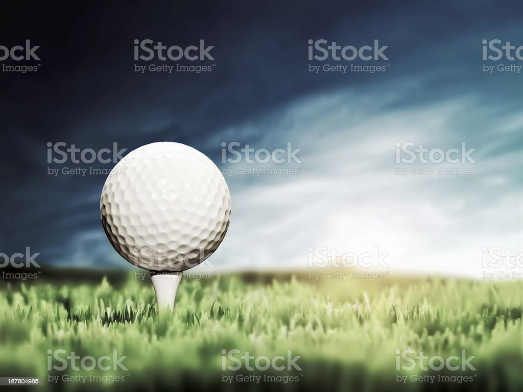 Golf ball placed on white golf tee on green grass golf course. Moody...
