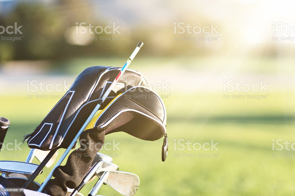 Close-up of golf clubs in golf bag on course stock photo