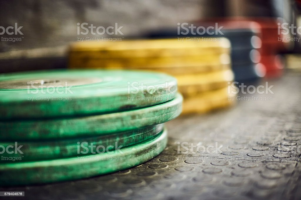Close-up of green barbell plates on floor stock photo