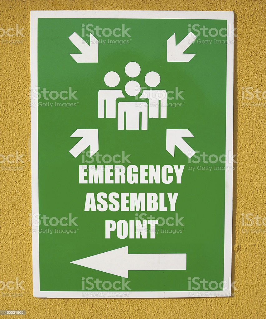 Closeup of green sign pointing right to emergency assembly stock photo