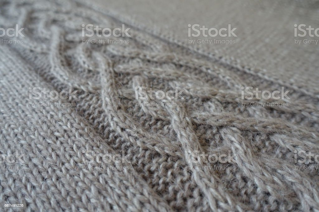 Close-up of grey handmade knit fabric with plait pattern stock photo