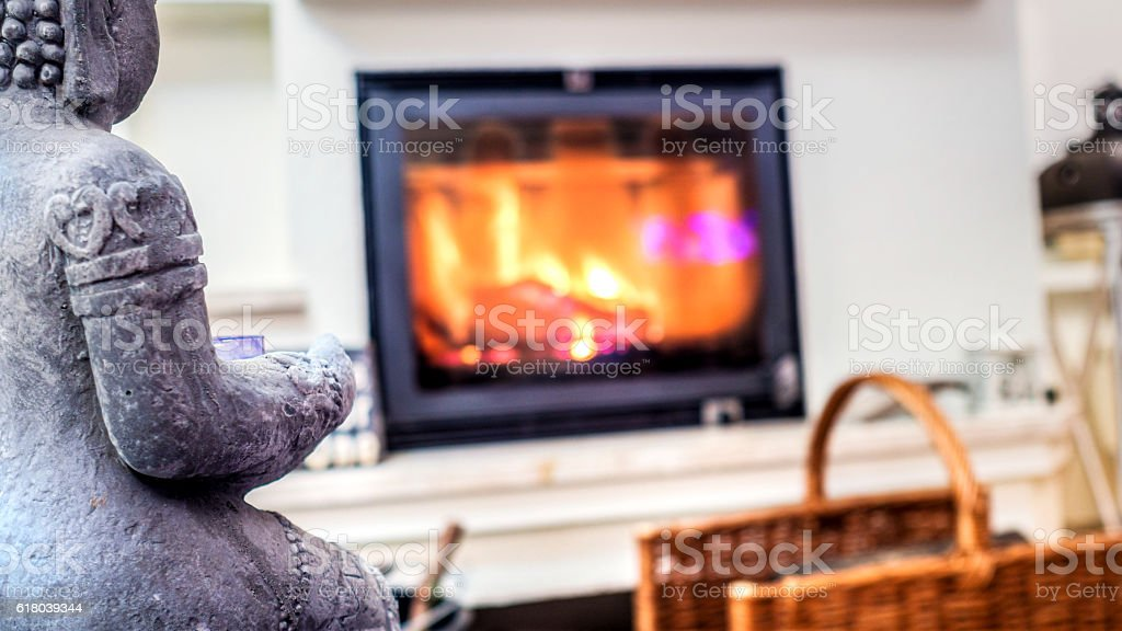 closeup of grey statue with fire place as blurred background stock photo