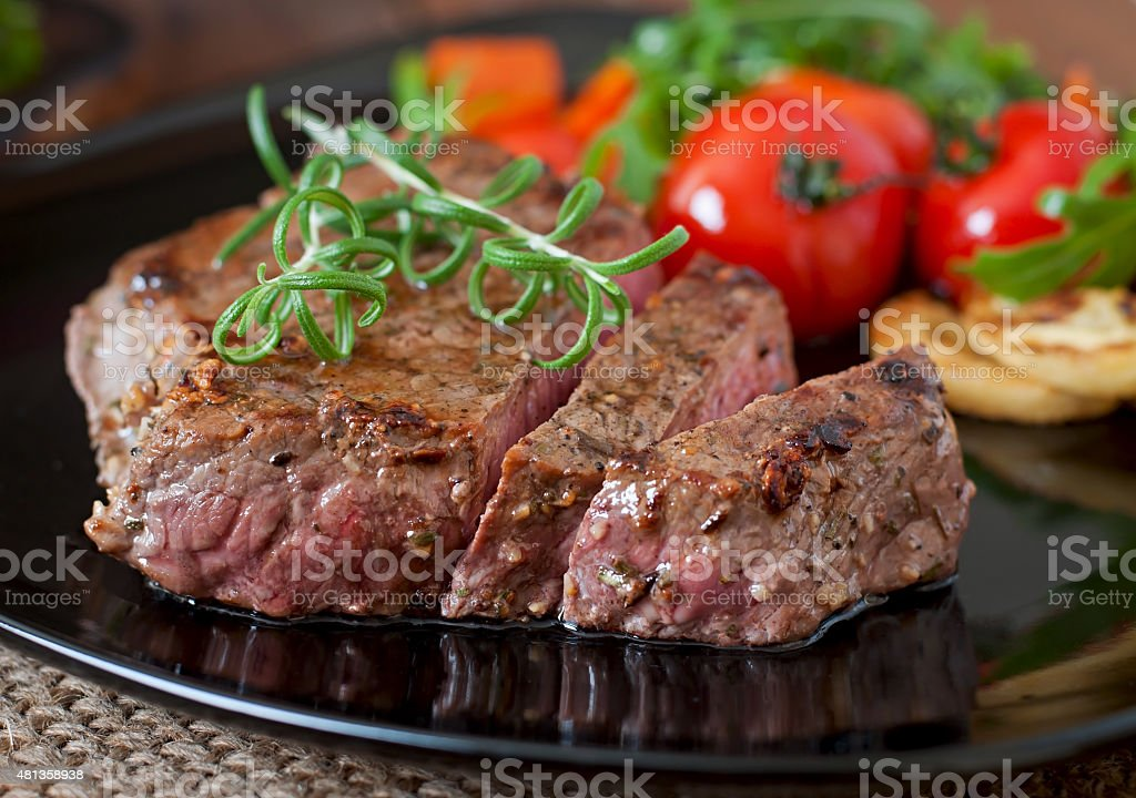 Closeup of grilled beef steak with vegetables stock photo