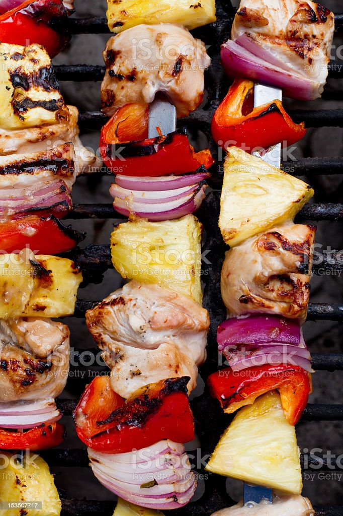 Close-up of grilled chicken, vegetable and pineapple kabobs stock photo