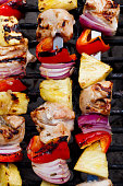 Close-up of grilled chicken, vegetable and pineapple kabobs