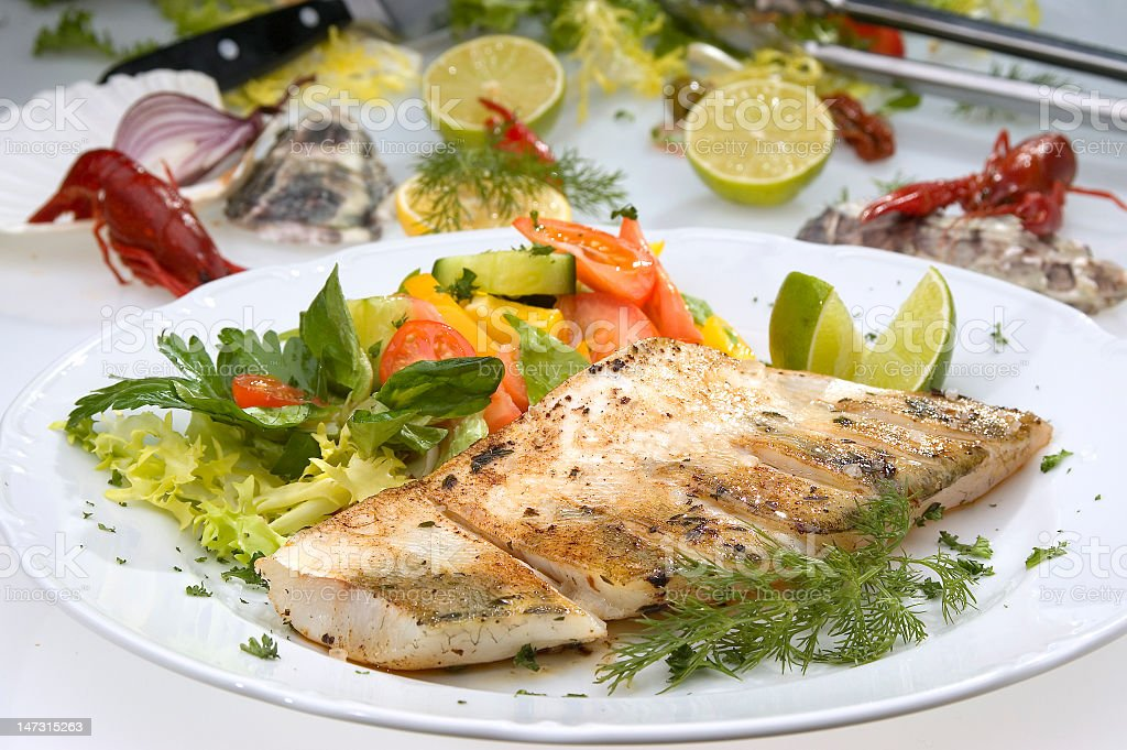 Close-up of grilled pikeperch on a white dish with salad stock photo