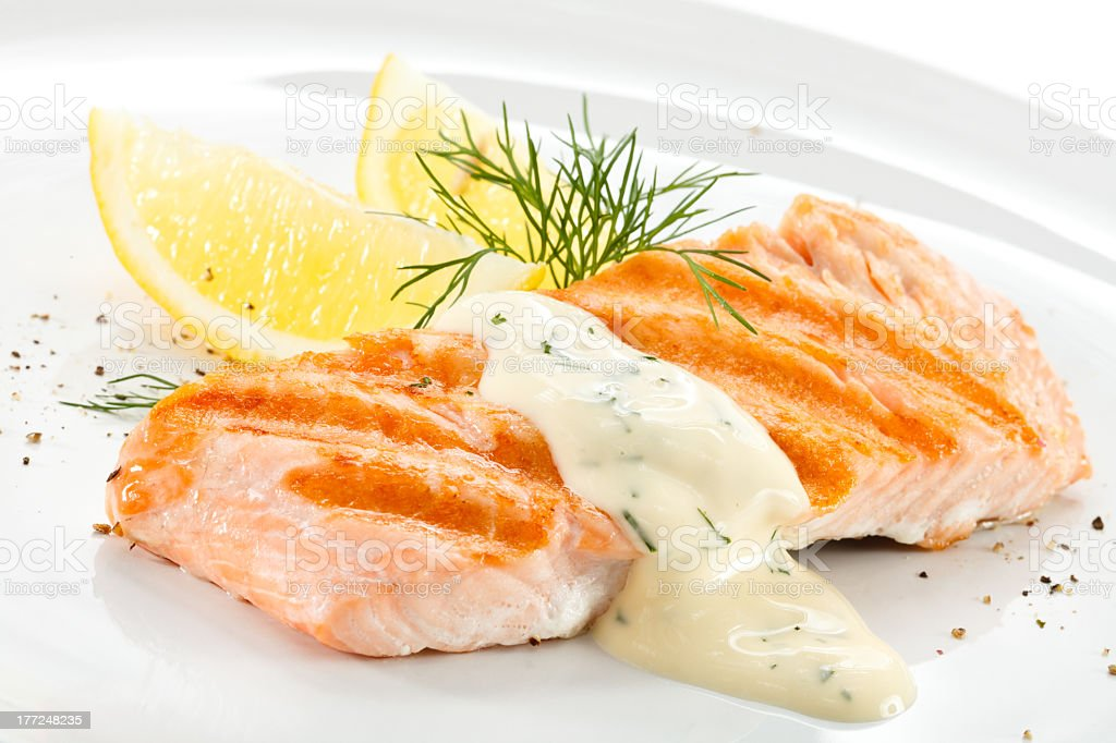 Close-up of grilled salmon with hollandaise, lemon and dill stock photo
