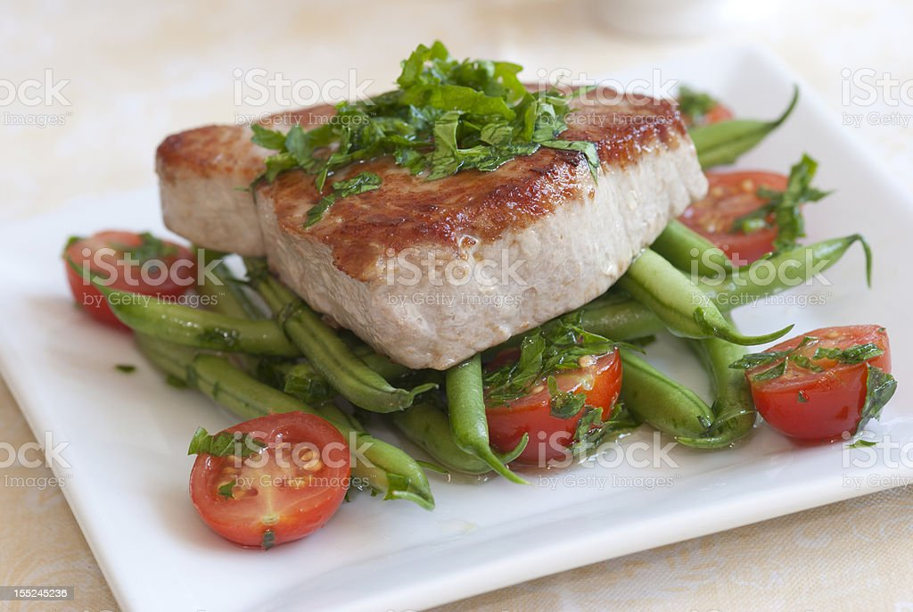 Close-up of grilled tuna steak on tomatoes and sword beans stock photo