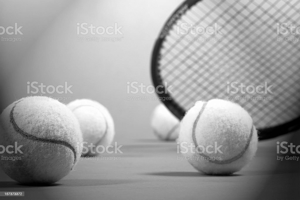 Close-up of group of tennis balls and tennis racket stock photo
