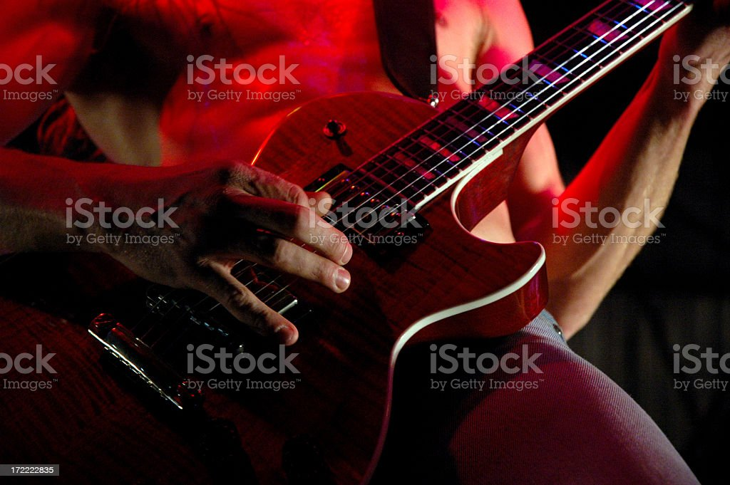 Close-up of guitarist playing the guitar illuminated in red royalty-free stock photo
