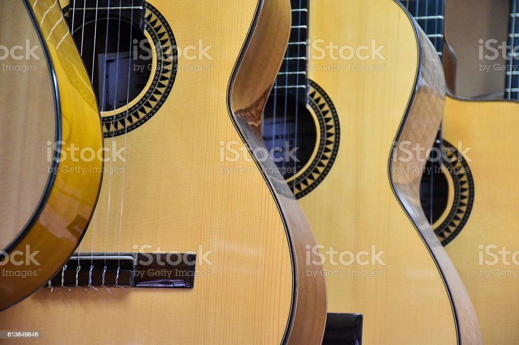 Closeup of guitars lined up in a music store stock photo