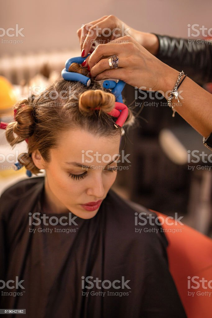Close-up of hairdresser putting curlers on woman's hair. stock photo