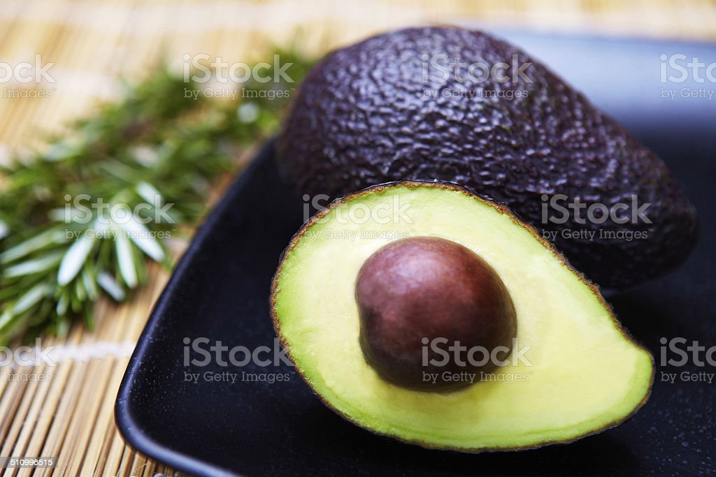 Close-up of Halved Avocado on a Black Plate stock photo