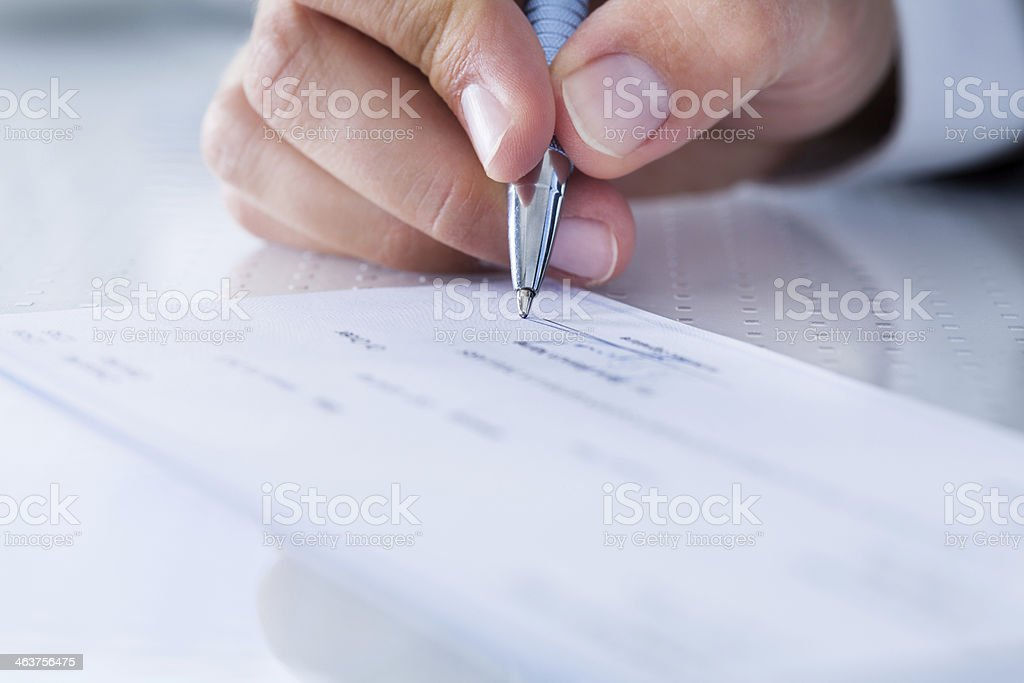 Close-up Of Hand Filling Cheque stock photo