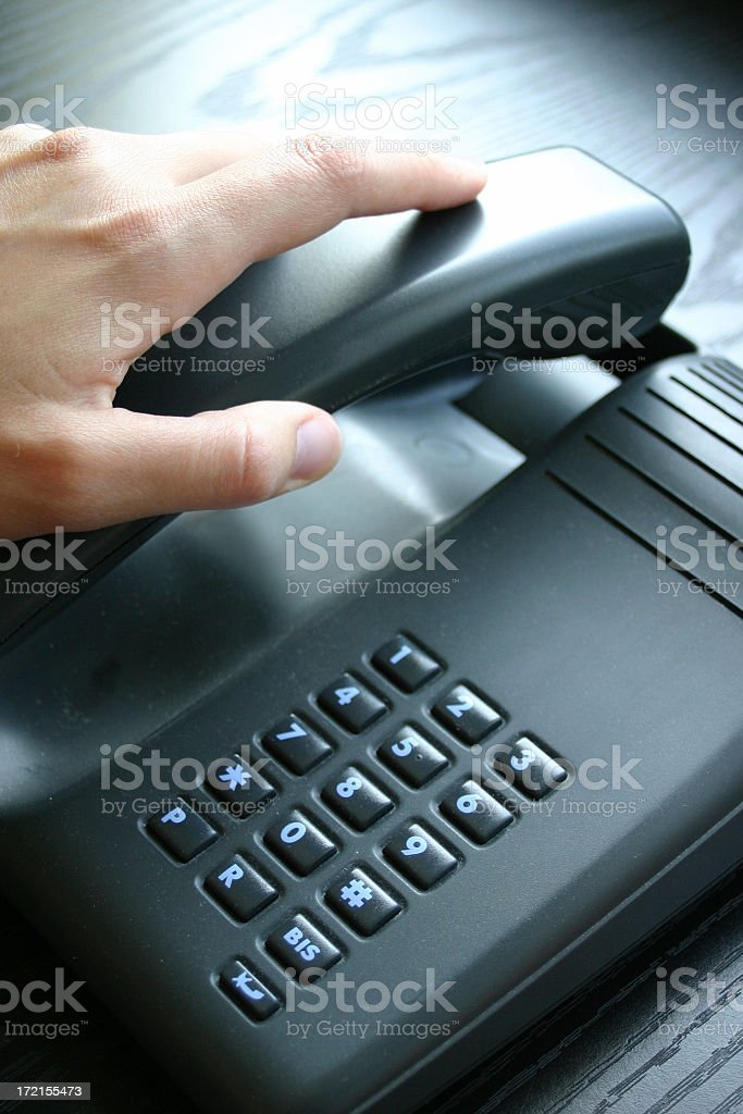 Close-up of hand hanging up a black phone stock photo