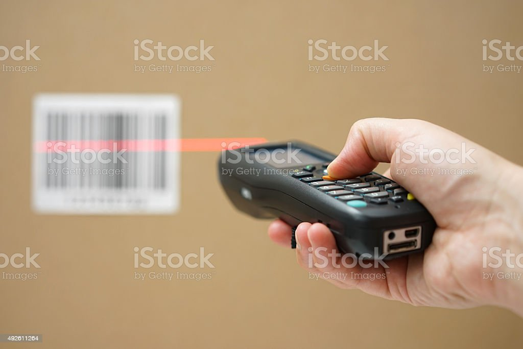 closeup of hand holding bar code scanner and scanning code stock photo