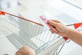 Close-up of hand holding credit card and pushing shopping trolley