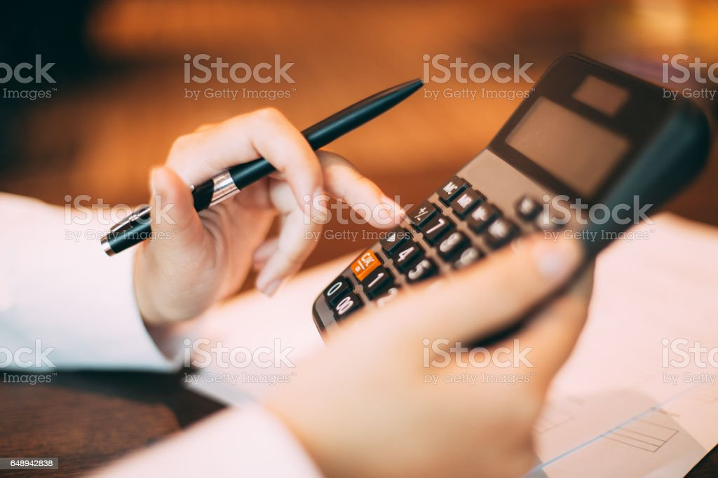 Close-up of hand holding pen and using calculator stock photo
