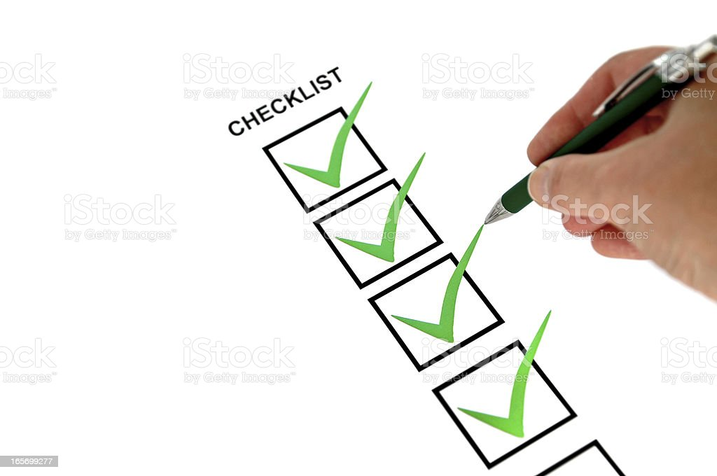 Close-up of hand holding pen making marks on a checklist royalty-free stock photo