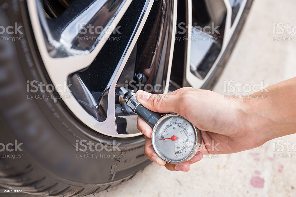 Closeup Of Hand holding pressure gauge for car tyre stock photo