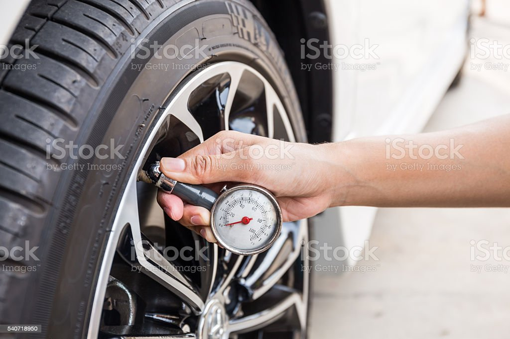 Close-Up Of Hand holding pressure gauge for car tyre stock photo