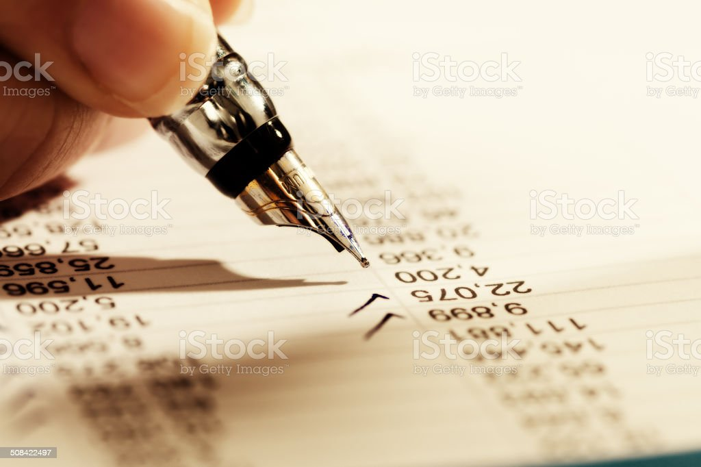 Close-up of hand making check marks on financial document royalty-free stock photo