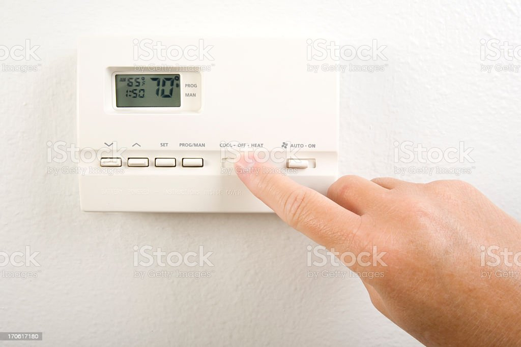 Close-up of hand operating the home heating system controls royalty-free stock photo