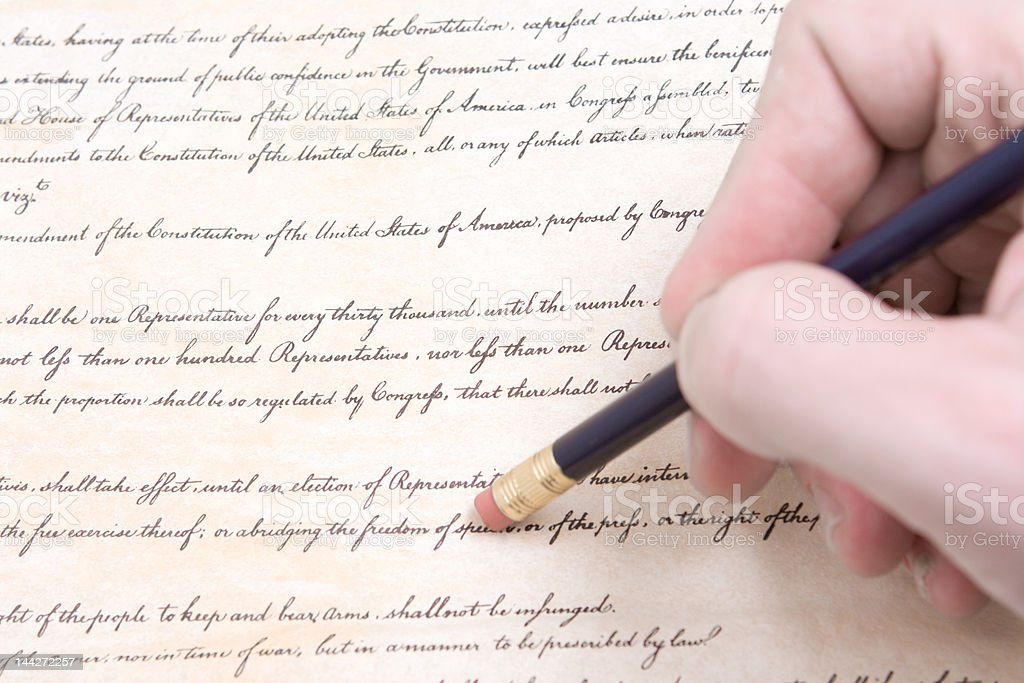 Closeup of Hand Pencil Erasing First Amendment to U.S. Constitution stock photo
